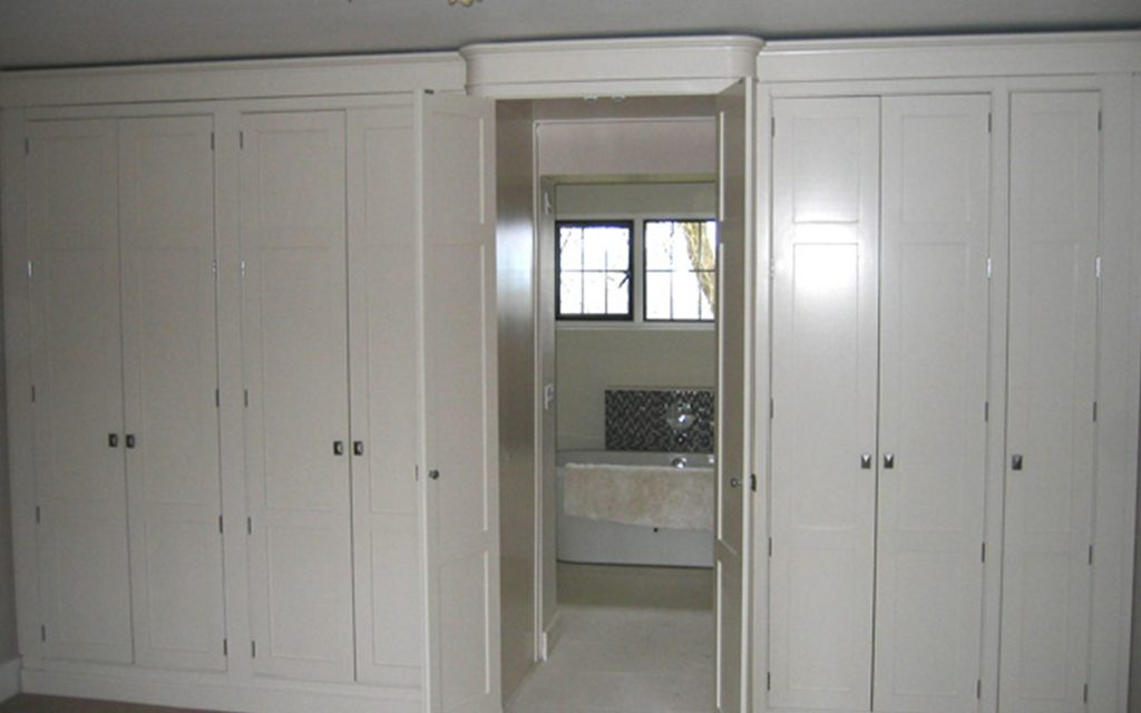 Fitted Walk-In Wardrobe with Concealed En Suite Entrance - Bourne's Fine Furniture
